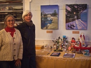 Woman artist with friend standing in front of art display
