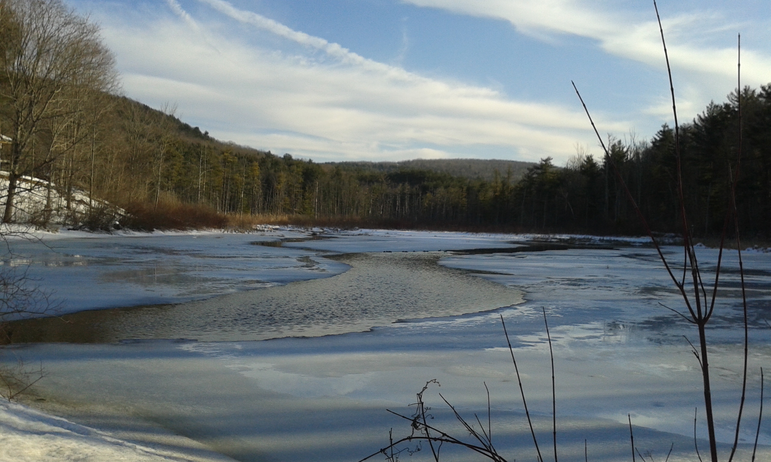 Partially open water with ice surround and hills in the distance